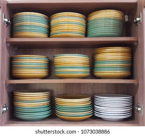 Colorful plates stacked in the kitchen cabinet