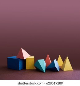 Colorful platonic solids, abstract geometric figures on violet background. Pyramid prism rectangular cube yellow blue pink green colored shapes. Shallow depth of field, copy space