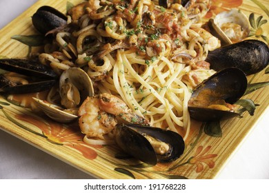 A colorful platter holds seafood fra diavolo over linguine.  Fresh littleneck clams, mussels, shrimp, and squid are piled over the linguini with fresh basil sprinkled on top.