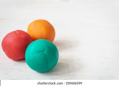 colorful playdough balls on wooden table.