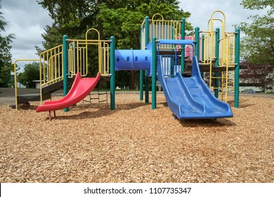 Colorful playground equipment with slides, ladders, crawl tubes in a bed of wood chips
