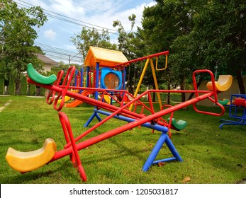 colorful playground on yard in the park. activities in public park. surrounded  by green trees. seesaw on modern playground.