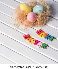 Colorful polka dot eggs in a nest with 'Happy Easter' text on white wooden background