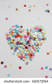 Colorful polka dot papers with heart shape on white background.