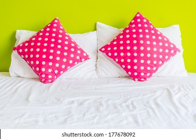 a1fff91a59 Colorful polka pillow on white bed