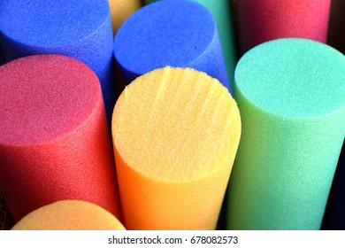 colorful pool noodles, aerobics and aqua gym noodle close up view