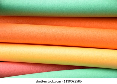 colorful pool noodles in different pastel colors, pool or therapy or swim noodles in modern colors detail shot