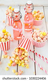Colorful popcorn in striped cups and lemonade in vintage bottles