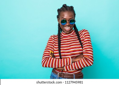 Colorful portrait of amazing woman in red shirt with afro hairstyle looking on camera with smile isolated over blue background