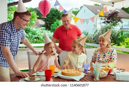 Colorful portrait of happy big family celebrate birthday and grandparents blows candles with their children
