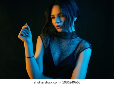Colorful portrait of a sensual beautiful brunette woman in a sexy fashion dress posing on a black background in studio