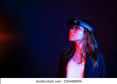 Colorful portrait of young asian business women try augmented and virtural reality glasses hololens in the lab room. Mixed reality future technology concept. Feminism power in world technology