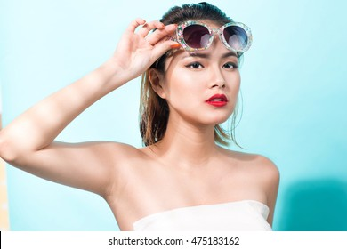 Colorful portrait of young attractive asian woman in sexy dress and wearing sunglasses over blue background. Summer beauty concept