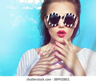 Colorful portrait of young attractive woman wearing sunglasses. Summer beauty and nail art concept