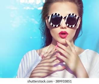 Farbiges Porträt einer jungen attraktiven Frau, die eine Sonnenbrille trägt. Konzept der Sommerbeauty und Nagelkunst