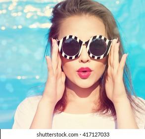 Farbiges Porträt einer jungen attraktiven Frau, die eine Sonnenbrille trägt. Schönheitskonzept im Sommer