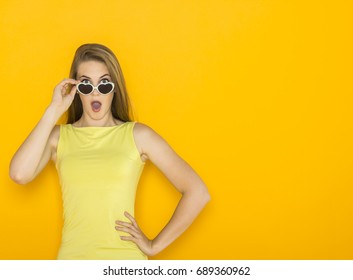 Colorful portrait of young attractive woman wearing sunglasses in hearts form and evaluates something. Summer beauty concept on orange background