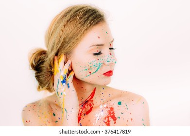 Colorful portrait of young woman  in paint with red lips and closed eyes on white background