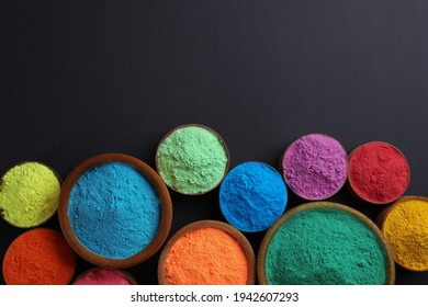 Colorful powders in bowls on black background, flat lay with space for text. Holi festival celebration
