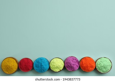 Colorful powders in bowls on light background, flat lay with space for text. Holi festival celebration