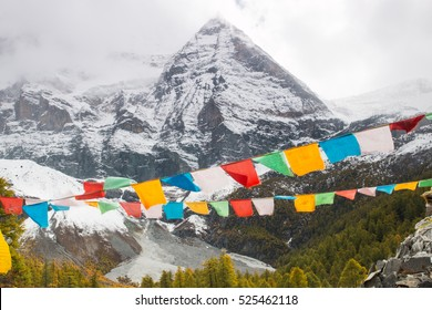 Colorful prayer flag at Yading National Park in autumn with a beautiful snow mountain. Daocheng, Sichuen, China.