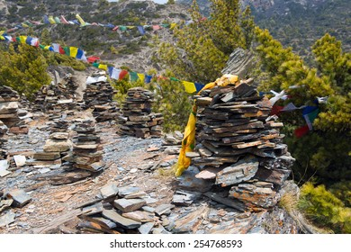 Colorful prayer flags and cairn on a Annapurna Circuit - most popular tourists trek in Himalayan mountain massive in Nepal.