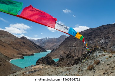 Colorful prayer flags fly high over the Tibetan landscape.
