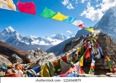 Colorful prayer flags on the Everest Base Camp trek in Himalayas, Nepal. View of Mount Ama Dablam and Mount Kangtega.