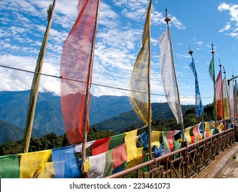 Colorful prayer flags over a clear blue sky near a temple in Bhutan with a view over the Himalayen mountains