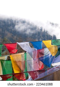 Colorful prayer flags over the misty himalayas at the Dochula Pass between Punakha and Thimpu in Bhutan