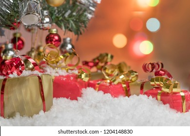 Colorful presents lying in the fake snow under the Christmas tree and colorful lights in the background