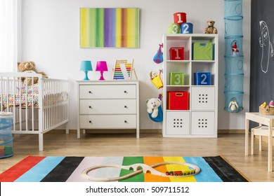 Colorful and pretty child room with chest of drawers and cradle