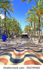 Colorful promenade under tall palm trees near the harbor of Alicante, Spain
