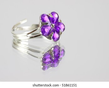 Colorful purple costume jewelry ring on mirrored surface