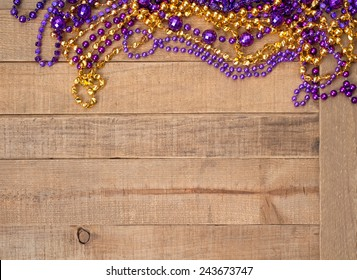 Colorful Purple and Gold Mardi Gras Beads on rustic wood board background with room or space for copy, text, your words.  Horizontal.  Louisiana State University school colors.