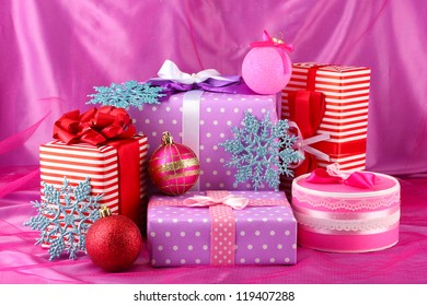 Colorful purple, red and pink gifts with Christmas balls and snowflakes on pink background