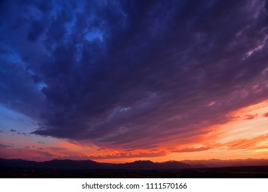 colorful purple-hued sunset over the front range of the colorado rocky mountains, as seen from broomfield, colorado