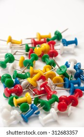 Colorful push pins on the white background.