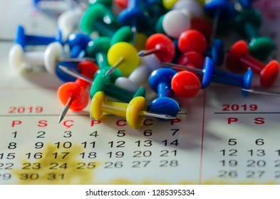 Colorful pushpins on a calender. School or business concept