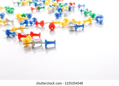 Colorful pushpins on white.