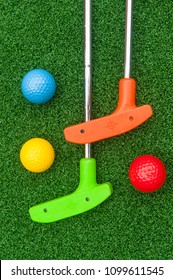 Colorful putt putt clubs and balls on artificial turf
