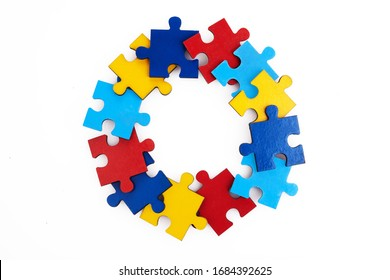 Colorful puzzles round frame on white background, early childhood autism concept, copy space, text space.