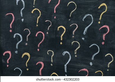 Colorful question marks on chalkboard background. Close up.