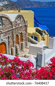 Colorful quiet backyard with beautiful pink flowers and classic traditional architecture in Santorini, Fira, Greece