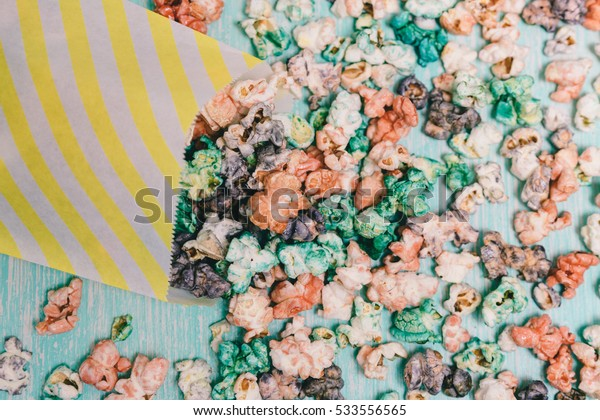 Colorful rainbow candy popcorn. Fruit flavored popcorn in yellow paper bag. Sugared popcorn texture