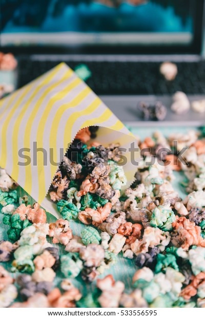 Colorful rainbow candy popcorn.  Fruit flavored popcorn in yellow paper bag. Sugared popcorn texture. Background with cinema on the tablet