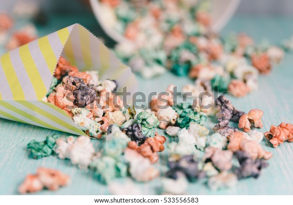 Colorful rainbow candy popcorn.Fruit flavored popcorn in yellow paper bag. Sugared popcorn texture