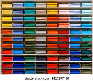 Colorful rainbow clothes background .Various vibrant color shirts perfectly folded on a shelf in the shop. Colored male clothes displayed in store. T-shirt of different color are neatly stacked in a