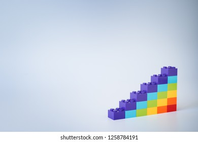 Colorful rainbow colored ascending stacks made of toy building bricks on gray background. Copy space.