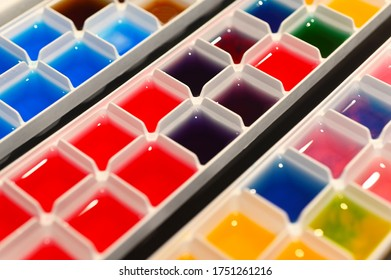 Colorful rainbow colors ice cubes in multi compartments tray served on a rainbow theme birthday party.